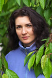 Mooie vrouw die zich dichtbij van een kersenboom bevinden Stock Foto