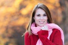 Mooie vrouw die zich in een park in de herfst bevindt Stock Afbeeldingen
