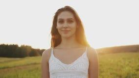Mooie vrouw die zich in een weide op de zomeravond bevinden Lang haar die in wind in zonneschijn bij zonsondergang stromen stock video