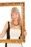 Mooie vrouw die zich met frame en het glimlachen bevindt Royalty-vrije Stock Foto's
