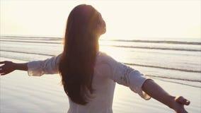 Mooie vrouw die zich met wapens uitgestrekt op kust bevinden stock footage