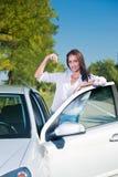 Mooie vrouw die zich naast de sleutels van een autoholding bevinden Stock Foto's