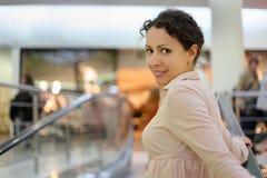 Mooie vrouw die zich op roltrap bevindt royalty-vrije stock foto's