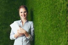 Mooie vrouw die zich over een groene grasmuur bevinden, die een tablet houden royalty-vrije stock foto