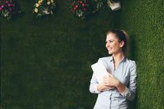 Mooie vrouw die zich over een groene grasmuur bevinden, die een tablet houden stock fotografie
