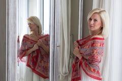 Mooie Vrouw die zich voor Spiegel bevindt Royalty-vrije Stock Fotografie