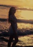 Mooie vrouw die zich in zeewater bevinden en op zonsondergang kijken brig stock foto