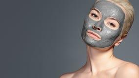 Mooie Vrouw die Zwart Gezichtsmasker toepassen Schoonheidsbehandelingen Het kuuroordmeisje past Clay Facial-masker op grijze acht royalty-vrije stock foto's