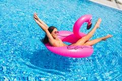 Mooie vrouw, die zwempak dragen, die op een roze matras van de flamingolucht in een pool van blauw water, de zomer liggen stock fotografie