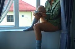 Mooie vrouw door het venster Stock Foto