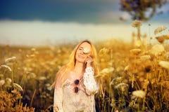 Mooie vrouw in een bloemweide met zonnebril en bloem, verlangen voor het leven Stock Foto's