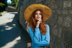 Mooie vrouw in een grote hoed met een grijns op de straatachtergrond stock fotografie