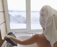 Mooie vrouw in een hete ton Jacuzzi in het hotel, panorama van het venster in de badkamers royalty-vrije stock fotografie