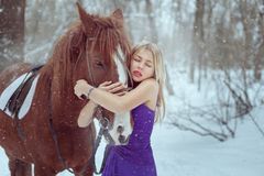 Mooie vrouw in een kleding die een paard koesteren royalty-vrije stock foto