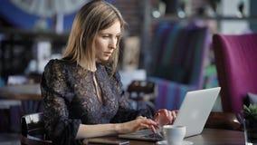 Mooie vrouw in een koffie die met laptop werken De ernstige bedrijfsdame, voert online een orde tijdens middagpauze uit stock videobeelden