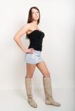 Mooie vrouw in een korte denimrok, een korte bovenkant en laarzen Stock Fotografie