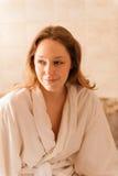 Mooie vrouw in een kuuroord die een witte robe dragen die op een massa wachten Stock Afbeeldingen