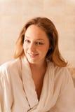 Mooie vrouw in een kuuroord die een witte robe dragen die op een massa wachten Stock Fotografie