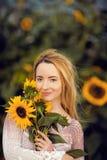 Mooie vrouw in een landelijke gebiedsscène in openlucht, met zonnebloemen Stock Foto