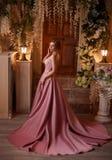 Mooie vrouw in een luxueuze roze kleding stock afbeelding
