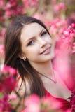 Mooie vrouw in een park met roze bloemen royalty-vrije stock afbeelding