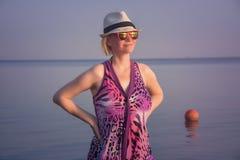 Mooie vrouw in een purpere kleding die zich in het water met aardige zonsondergang bevindt stock foto's