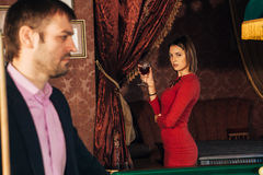 Mooie vrouw in een rode kleding die op het spel van Biljart letten stock afbeelding