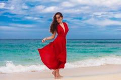 Mooie vrouw in een rode kleding die zich op de overzeese kust bevinden Stock Afbeeldingen