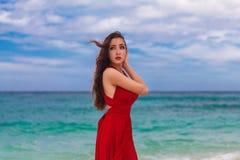 Mooie vrouw in een rode kleding die zich op de overzeese kust bevinden Stock Foto's