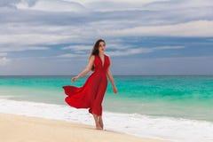 Mooie vrouw in een rode kleding die zich op de overzeese kust bevinden Stock Foto
