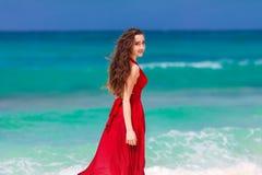 Mooie vrouw in een rode kleding die zich op het tropische mede overzees bevinden Stock Fotografie
