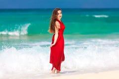 Mooie vrouw in een rode kleding die zich op het tropische mede overzees bevinden Stock Afbeeldingen
