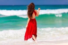 Mooie vrouw in een rode kleding die zich op tropische overzeese coa bevinden Stock Foto's