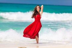 Mooie vrouw in een rode kleding die zich op tropische overzeese coa bevinden Stock Foto
