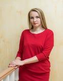 Mooie vrouw in een rode kleding tegen de muur Stock Afbeelding
