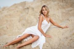 Mooie vrouw in een witte kleding in een woestijn Stock Afbeeldingen