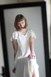 Mooie Vrouw in een Witte Kleding in Nagedacht in een Spiegel stock fotografie