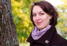 Mooie vrouw en de herfstbladerenachtergrond Royalty-vrije Stock Afbeelding