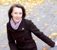 Mooie vrouw en de herfstbladerenachtergrond Royalty-vrije Stock Afbeeldingen
