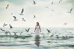Mooie vrouw en seaguls op het strand Stock Afbeelding