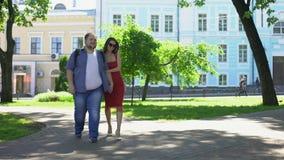 Mooie vrouw en vette man holdingshanden die in park, droom lopen, vrije tijd stock videobeelden