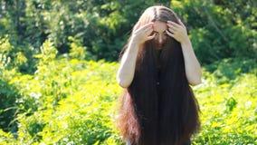 Mooie vrouw en zorgen over haar lang haar op een zonnige de zomerdag stock videobeelden