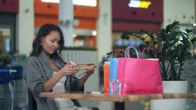 Mooie vrouw finishig het winkelen dag in koffie, die nieuwe schoenen bekijken stock videobeelden