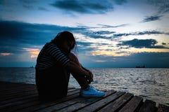 Mooie vrouw in gefrustreerde depressiezitting op houten bridg stock afbeeldingen