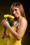 Mooie vrouw in gele kleding met roze bloemen Royalty-vrije Stock Foto's