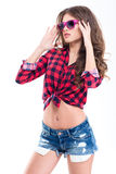 Mooie vrouw in geruit overhemd, jeansborrels en roze zonnebril Stock Afbeelding