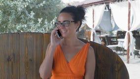 Mooie vrouw in glazen die op de telefoon en het glimlachen zitting in de koffie op de overzeese kust spreken stock footage