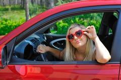 Mooie vrouw in hart gevormde glazen in auto royalty-vrije stock foto