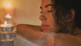Mooie vrouw in het bad door het kaarslicht stock video