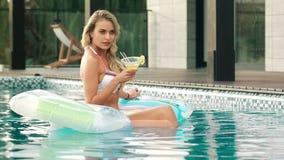 Mooie vrouw het drinken cocktail op opblaasbare matras in pool stock videobeelden